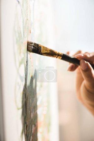 Foto de Vista recortada de la chica dibujo con pintura verde y pincel - Imagen libre de derechos
