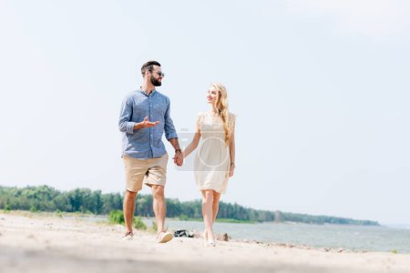 Photo for Adult couple walking along beach, talking and holding hands - Royalty Free Image