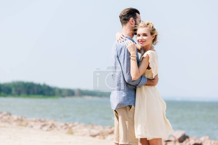 Photo for Smiling blonde woman hugging bearded boyfriend at beach - Royalty Free Image