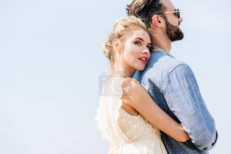 Photo for Young beautiful blonde woman hugging bearded boyfriend with clear sky on background - Royalty Free Image