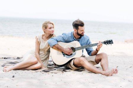 Photo pour Belle jeune femme pieds nus s'asseyant sur la couverture avec le petit ami jouant la guitare acoustique à la plage près de la mer - image libre de droit