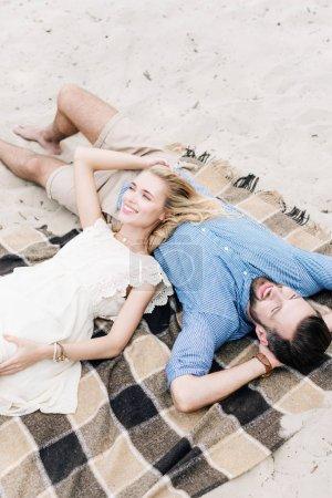 Foto de Happy couple lying together on checkered blanket at sandy beach - Imagen libre de derechos