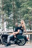 "Постер, картина, фотообои ""side view of sexy couple of bikers on black motorcycle on road near green forest"""