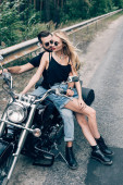 """Постер, картина, фотообои """"young couple of bikers sitting on black motorcycle on road near green forest"""""""