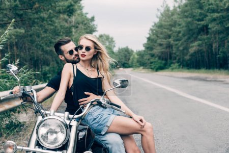Photo pour Young couple of bikers closely sitting on black motorcycle on road near green forest - image libre de droit