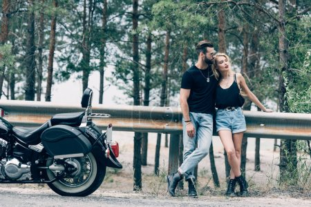 Photo pour Young couple of bikers embracing near black motorcycle on road near green forest - image libre de droit