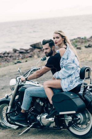 Photo pour Jeune couple de motards assis sur une moto noire à la plage près de la rivière - image libre de droit