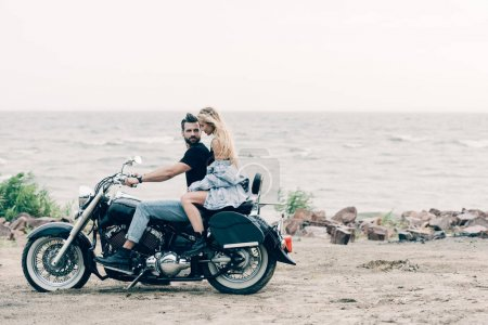 Photo pour Side view of young couple of bikers on black motorcycle near river - image libre de droit