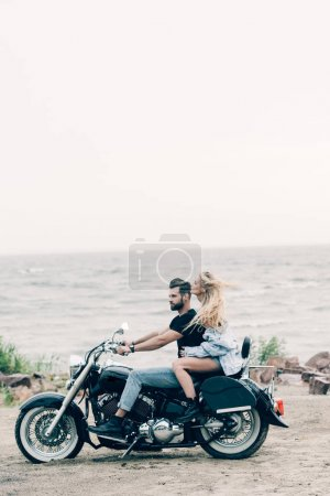 Photo pour Side view of young couple of bikers riding black motorcycle at sandy beach near river - image libre de droit