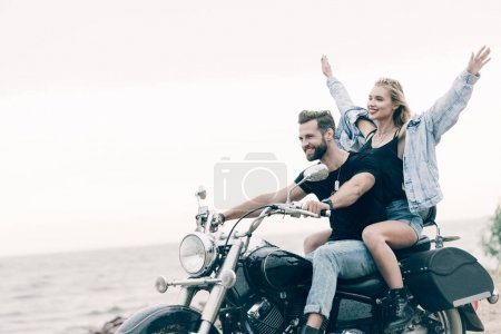 Photo pour Smiling young couple of bikers riding black motorcycle while girl putting hands in air near river - image libre de droit