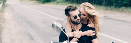 young couple of bikers closely embracing on black motorcycle, panoramic shot