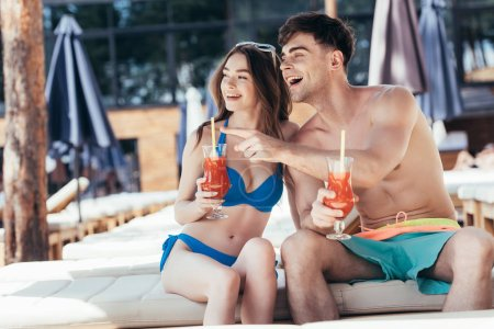 Photo for Cheerful young man pointing with finger while sitting on deck chair near attractive girlfriend - Royalty Free Image