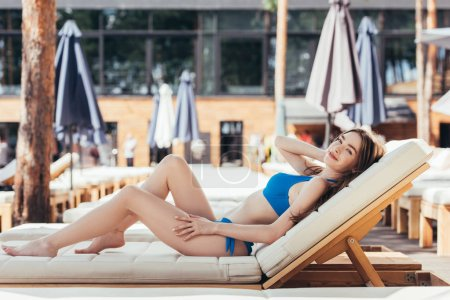 Photo for Happy young woman relaxing on chaise lounge and smiling at camera - Royalty Free Image