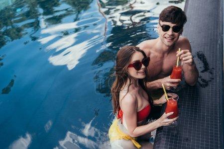 Photo pour Joyeux jeune couple tenant des verres de boisson rafraîchissante et souriant à la caméra - image libre de droit