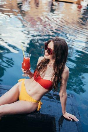 Photo pour Belle jeune femme en maillot de bain tenant un verre de boisson rafraîchissante tout en étant assis au bord de la piscine - image libre de droit