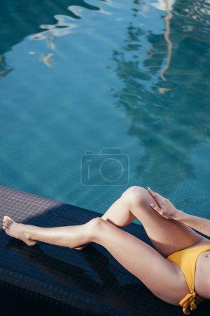 Photo pour Vue partielle de jeune femme prenant un bain de soleil tout en se trouvant près de la piscine - image libre de droit