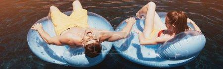 Photo pour Tir panoramique de jeunes couples bronzer sur des anneaux de natation dans la piscine - image libre de droit