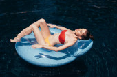 """Постер, картина, фотообои """"красивая молодая женщина в купальнике загорать на плавать кольцо в бассейне"""""""