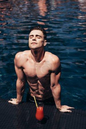 Photo pour Bel homme joyeux bronzer sur le bord de la piscine avec les yeux fermés près d'un verre de boisson rafraîchissante - image libre de droit