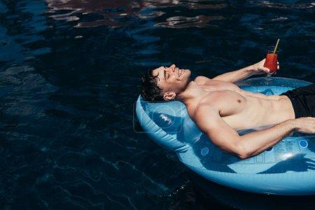 Photo pour Jeune homme heureux détendant sur l'anneau de natation dans la piscine avec le verre de boisson rafraîchissante - image libre de droit