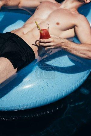 Photo pour Vue partielle de jeune homme détendant sur l'anneau de natation dans la piscine avec le verre de boisson rafraîchissante - image libre de droit