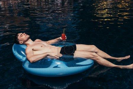 Photo pour Beau jeune homme prenant un bain de soleil sur l'anneau de natation dans la piscine avec le verre de boisson rafraîchissante - image libre de droit