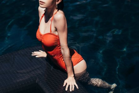Photo for Partial view of beautiful young woman in swimsuit relaxing on poolside - Royalty Free Image