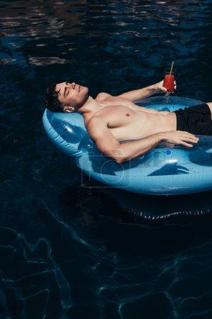 Photo pour Jeune homme beau retenant le verre de boisson rafraîchissante tout en flottant sur l'anneau de natation dans la piscine - image libre de droit