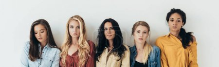 panoramic shot five multiethnic women looking at camera isolated on grey