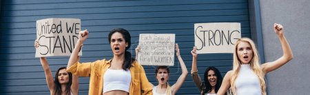 Photo for Panoramic shot of screaming multiethnic feminists holding placards with feminist slogans and showing fists up - Royalty Free Image