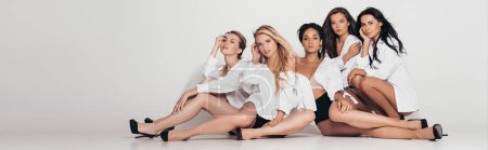 Photo for Panoramic shot of five sexy multiethnic feminists wearing white shirts and heels and sitting on grey - Royalty Free Image