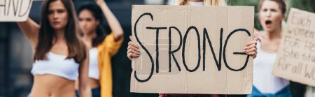 Photo for Panoramic shot of feminist holding placard with word strong near women - Royalty Free Image
