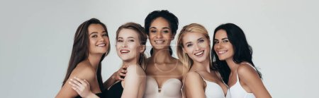 panoramic shot of five multiethnic girls smiling and looking at camera isolated on grey