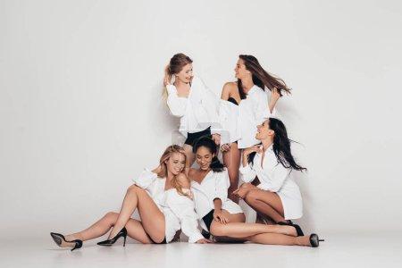 Photo pour Cinq féministes multiethniques sexy portant des chemises blanches et des talons noirs souriant tout en étant assis sur gris - image libre de droit