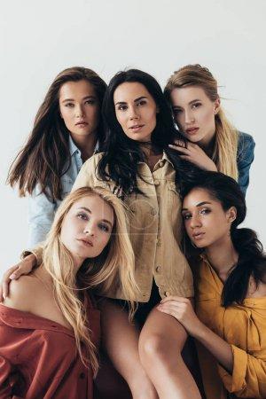 Photo pour Vue de face de cinq séduisantes féministes multiethniques en chemises colorées embrassant et regardant caméra isolée sur gris - image libre de droit