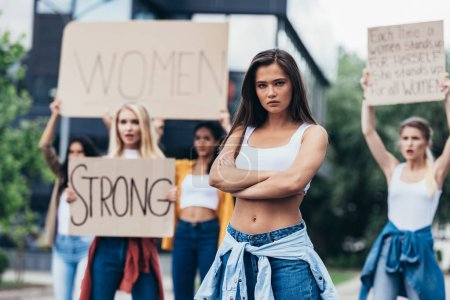 Photo for Serious feminist standing with arms closed near women holding placards with feminist slogans on street - Royalty Free Image