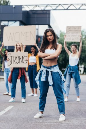 Photo pour Full length view of serious feminist standing with arms closed near women holding placards with feminist slogans on street - image libre de droit