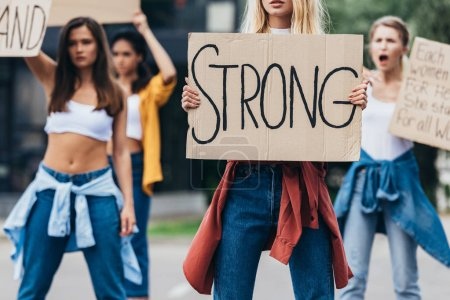 Photo for Cropped view of feminist holding placard with inscription strong near women on street - Royalty Free Image