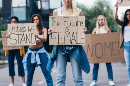 Photo for Cropped view of woman holding placard with inscription the future is female near feminists on street - Royalty Free Image