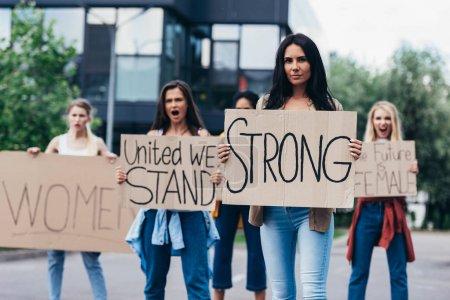 Photo pour Féministes criantre retenant des pancartes avec des slogans sur la rue - image libre de droit
