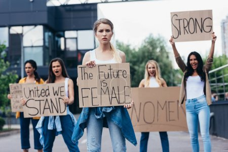 Photo for Screaming multiethnic feminists holding placards with slogans on street - Royalty Free Image