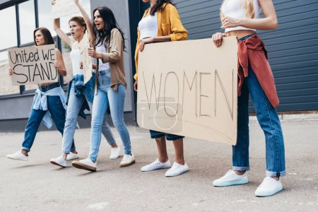 Photo for Cropped view of feminists holding placard with word women on street - Royalty Free Image
