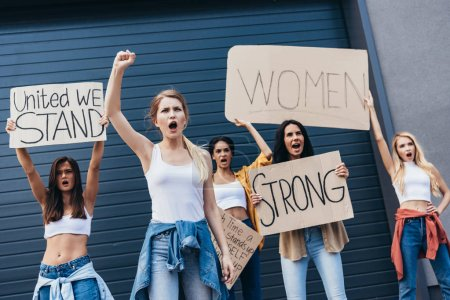 Photo for Five multiethnic feminists holding placards with slogans and screaming on street - Royalty Free Image