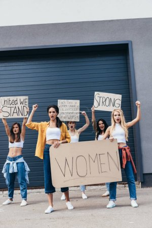 Photo for Full length view of screaming multiethnic feminists holding placards with slogans on street - Royalty Free Image