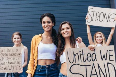 Photo pour Vue avant de sourire féministes multiethniques embrassant et tenant la plaque avec l'inscription unie nous nous tenons sur la rue - image libre de droit