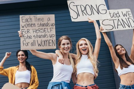 Photo for Four smiling multiethnic feminists embracing and holding placards with slogans on street - Royalty Free Image