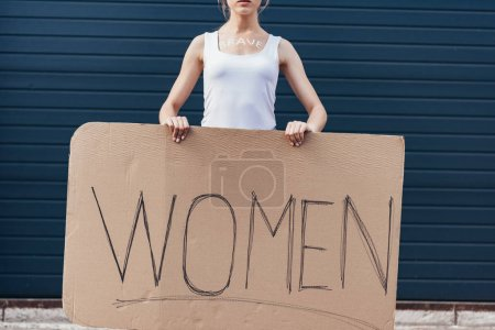 Foto de Vista recortada de feminista con palabra valiente en el cuerpo sosteniendo pancarta con mujeres inscripción en la calle - Imagen libre de derechos