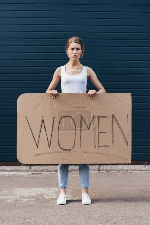 Photo for Full length view of feminist holding placard with word women on street - Royalty Free Image