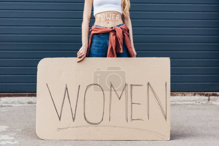 Photo for Cropped view of feminist with inscription power on belly holding placard with slogan women on street - Royalty Free Image