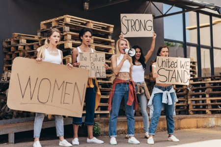 Photo for Full length view of five screaming multiethnic feminists with loudspeaker holding placards with slogans on street - Royalty Free Image